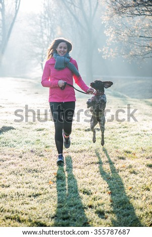 Runner woman and her cute German pointer dog running together outdoor at the beautiful park.  - stock photo