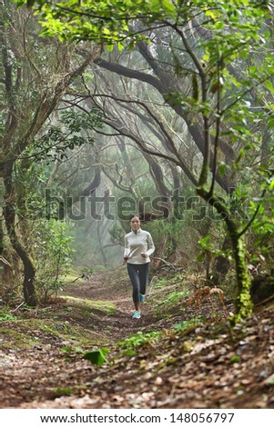 Runner woman cross-country running in beautiful forest trail run. Female athlete jogger training outdoor in amazing atmospheric forest nature landscape. Fit female fitness model with healthy lifestyle - stock photo