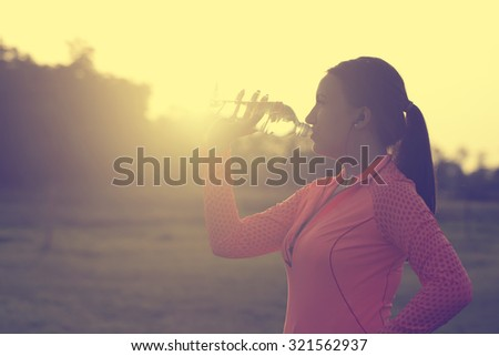 Runner woman drinking water - stock photo
