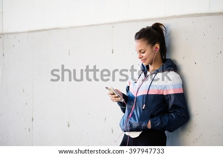 Runner woman listening to music on a break from training - stock photo