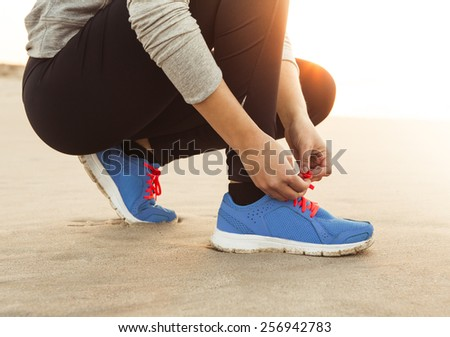Runner woman tying the shoelaces - stock photo