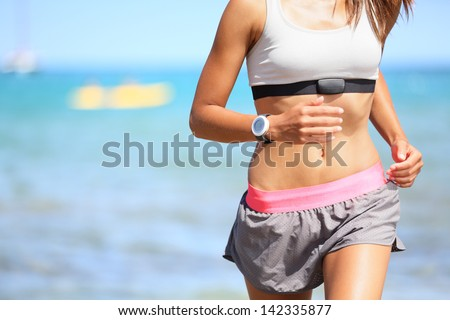 Runner woman with heart rate monitor running on beach with watch and sports bra top. Beautiful fit female fitness model training and working out outside in summer at part of healthy lifestyle. - stock photo