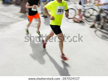 Runners in competition on bright summer day, with spectators enjoying themselves in the bright sunshine - stock photo