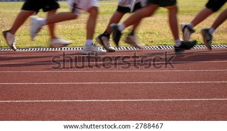 Runners in Motion -- exercising on an outdoor athletic running track - stock photo