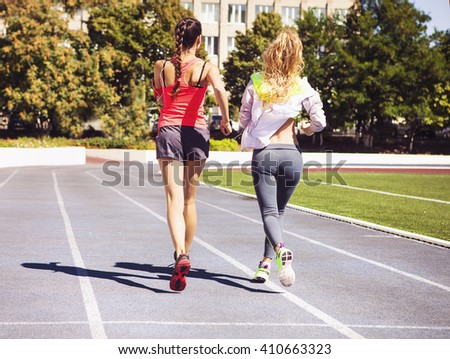 Runners on the stadium track. Women summer fitness workout. Jogging, sport, healthy active lifestyle and friendship concept - stock photo