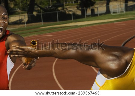 Runners Passing a Relay Baton - stock photo