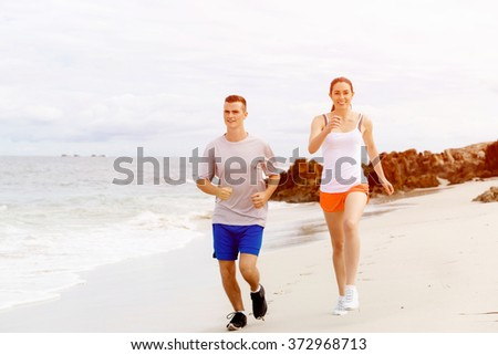 Runners. Young couple running on beach - stock photo