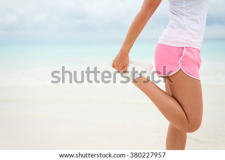 Running and fitness exercising lifestyle on summer concept. Woman stretching legs before working out towards the sea. - stock photo