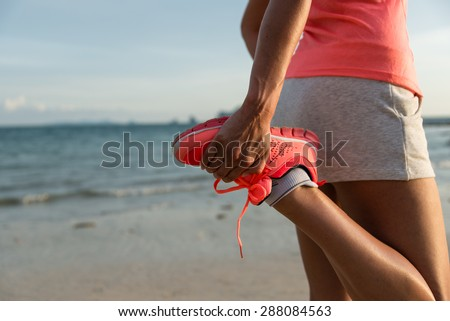 Running and healthy lifestyle concept. Runner footwear close up. Woman warming up for training at the beach. - stock photo