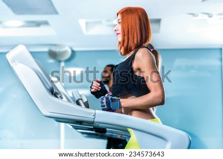 Running and movement. Sport and slender girl running on a treadmill. Athlete dressed in sports uniforms and running in the gym. - stock photo