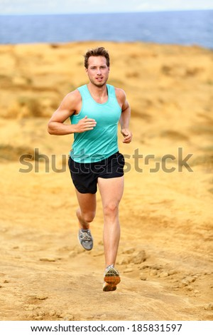 Running athlete man. Male runner cross country running and jogging training on trail outdoors on Big Island, Hawaii, USA - stock photo