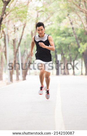 Running athlete man. Male runner sprinting at park - stock photo