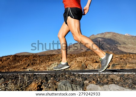 Running athlete man runner jogging on nature road in forest mountain. Lower half body running shoes and legs of male adult on a jog in summer. - stock photo