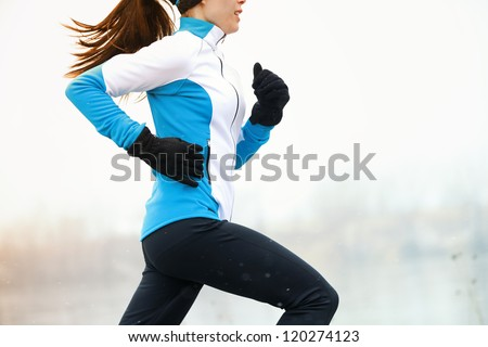 Running athlete woman sprinting during winter training outside in cold snow weather. Close up showing speed and movement. - stock photo