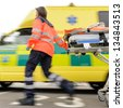 Running blurry paramedic woman rolling stretcher outside of ambulance car - stock photo