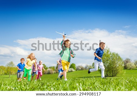 Running boy with airplane toy and other children - stock photo