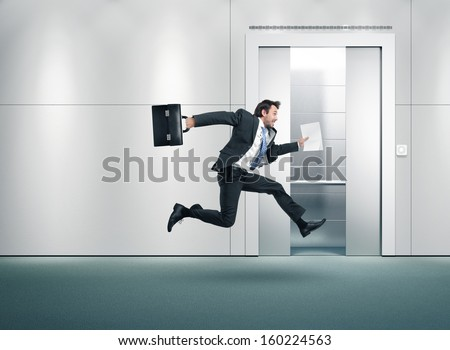 Running businessman and open lift door - stock photo