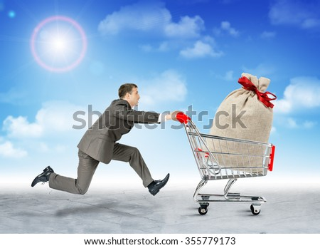 Running businessman with big bag in shopping cart - stock photo