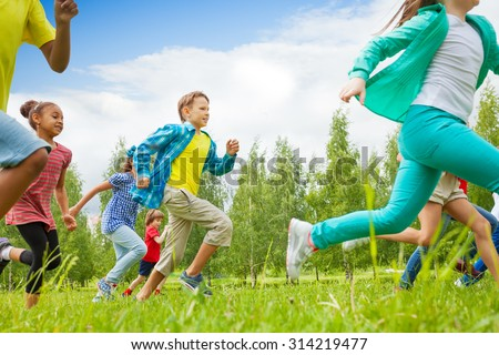 Running children view in the green field - stock photo