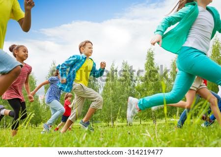Running children view in the green field - stock photo