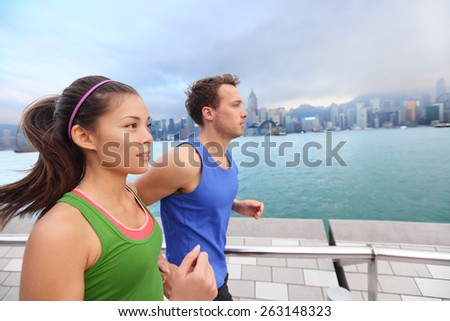 Running couple jogging in Hong Kong city. Runners training on Tsim Sha Tsui Promenade and Avenue of Stars in Victoria harbour, Kowloon, Hong Kong. Fitness runner man and sport woman model working out. - stock photo