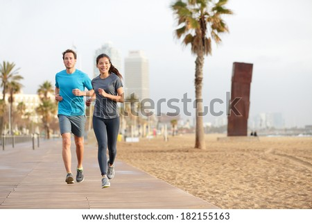 Running couple jogging on Barcelona Beach, Barceloneta. Healthy lifestyle people runners training outside on boardwalk. Multiracial couple, Asian woman, Caucasian fitness man working out, Spain. - stock photo