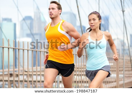 Running couple jogging training for New York marathon. Runners on run outside. Asian woman and Caucasian man runner and fitness sport models jogging on Brooklyn Bridge, New York City, USA. - stock photo