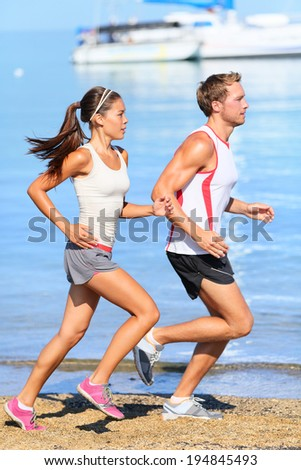 Running couple. Runners jogging on beach training together. Man and woman joggers exercising outdoors. - stock photo