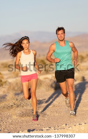 Running couple - runners jogging on trail run path outside in beautiful nature. Asian woman runner and Caucasian male fitness sport model jogger training together for cross-country marathon. - stock photo