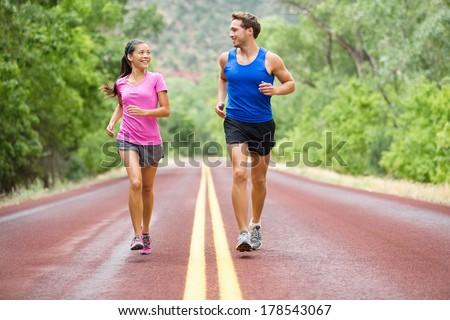 Running - exercising couple jogging and talking outside on road beautiful nature landscape. Runners training together for marathon run. Asian female sports woman and male fitness man in full body. - stock photo