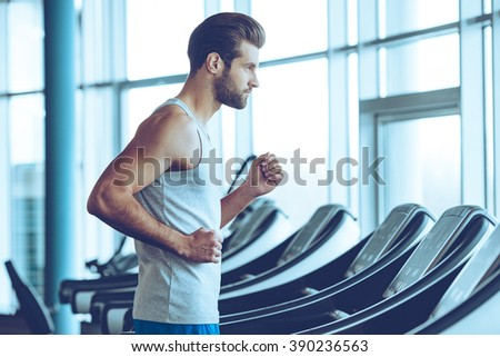 Running fast. Side view of young man in sportswear running on treadmill at gym - stock photo