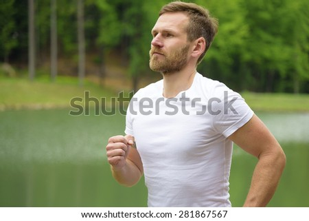 Running fitness man close-up sprinting outdoors in beautiful park.  - stock photo