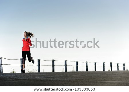 Running fitness training woman outdoors. Action healthy lifestyle image with copyspace - stock photo