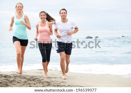 Running friends on beach jogging group training. Exercising runners training outdoors living healthy active lifestyle. Multiracial fitness runner people working out together outside smiling happy. - stock photo