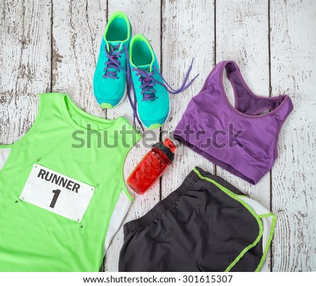 Running gear laid out ready for a race day, rustic wooden background - stock photo