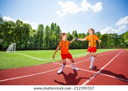 Running girl with baton hands it to other runner - stock photo