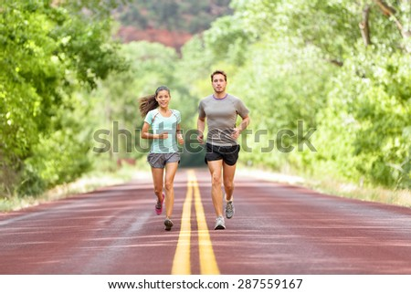 Running Health and fitness. Runners on run training during fitness workout outside on road. People jogging together living healthy active lifestyle outside in summer. Full body length of woman and man - stock photo