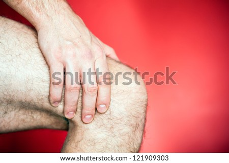 Running knee injury, runner leg pain, sore and exercising. Man holding sore knee, hand massage over red background. Fitness exercise concept. - stock photo