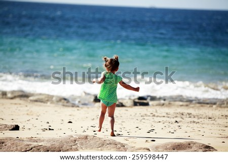 Running little girl on sandy beach - stock photo