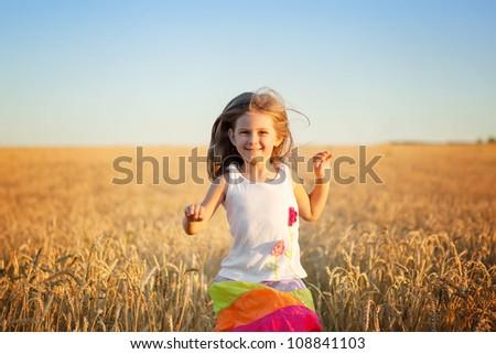 Running little happy girl   meadow weat field - stock photo