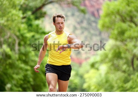Running looking at heart rate monitor smartwatch while running. Male runner jogging outside looking at sports smart watch during workout training for marathon run. Fit male fitness model in his 20s. - stock photo