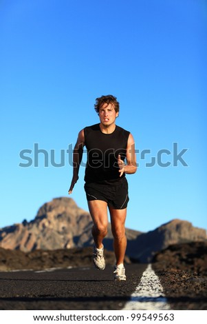 Running - male runner. Man sprinting during outdoor workout training session. Male caucasian athlete running on road in nature. - stock photo