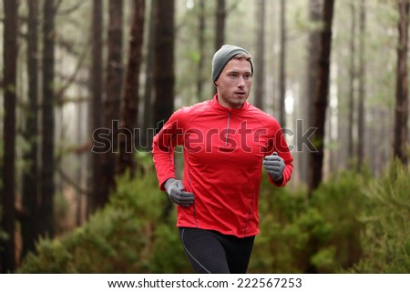 Running man in forest woods training and exercising for trail run marathon endurance race. Fitness healthy lifestyle concept with male athlete trail runner. - stock photo