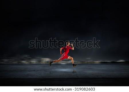 Running man in red sport wear on dark background - stock photo