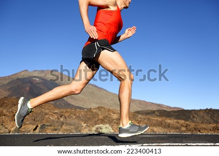 Running man - male runner training outdoors sprinting on mountain road in amazing landscape nature. Close up of fit handsome jogger working out for marathon outside in summer. - stock photo
