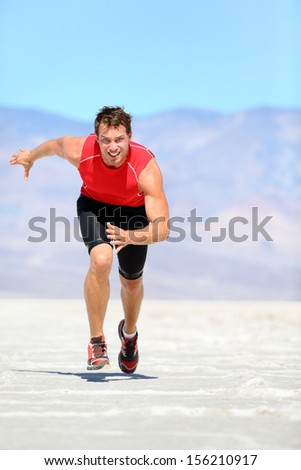 Running man - runner sprinting in desert nature. Fit athlete in fast sprint run at great speed towards camera. Male fitness model in amazing extreme desert landscape. - stock photo