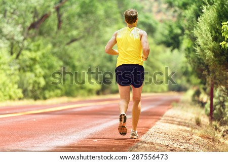 Running man runner working out for fitness. Male athlete on jogging run wearing sports running shoes and shorts working out for marathon. Full body length view showing back running away. - stock photo