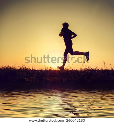 Running man silhouette in sunset time - stock photo
