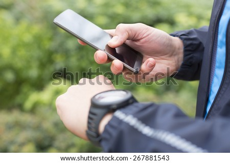 Running man with Mobile phone connected to a smart watch. Close-up hands - stock photo