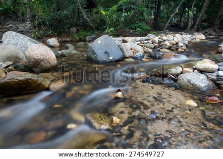 running of water stream from waterfall in tropical rain forest - stock photo